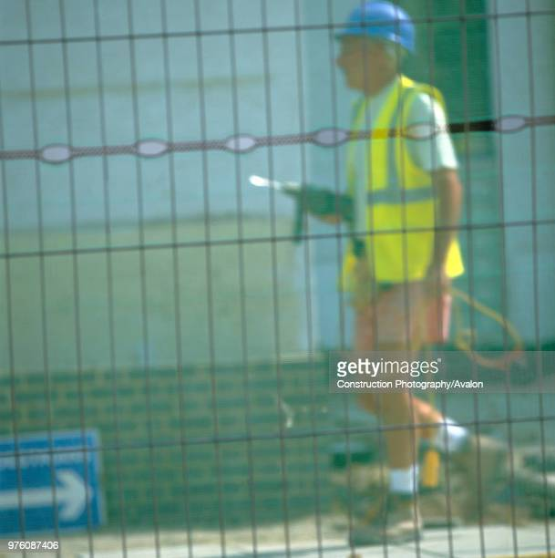 Worker walking with drill seen through security fence