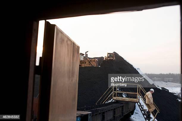 A worker walks across snow at a storage dump for coking coal at the Bielszowice mine operated by Kompania Weglowa SA in Ruda Slaska Poland on...