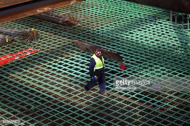 A worker walks across steel reinforcement laid down at Pier 4 in Boston where a ninestory 106unit residential building designed by internationally...
