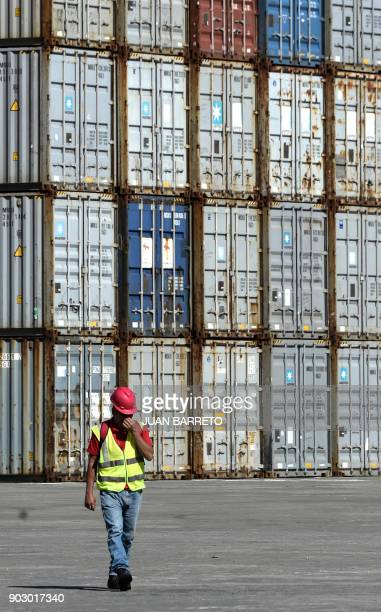 A worker walks along a container yard at the main port of 'La Guaira' in Caracas on January 9 2018 / AFP PHOTO / JUAN BARRETO