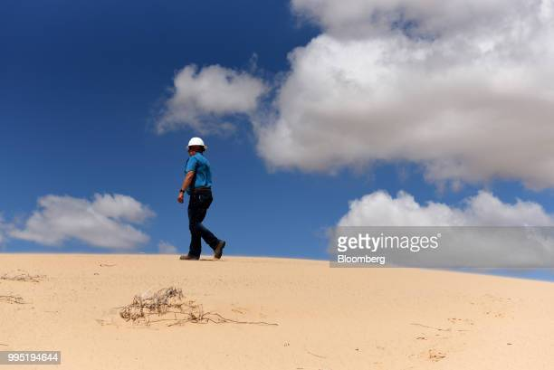 Worker walks along a sand dune at the Hi-Crush Partners LP mining facility in Kermit, Texas, U.S., on Wednesday, June 20, 2018. In the West Texas...