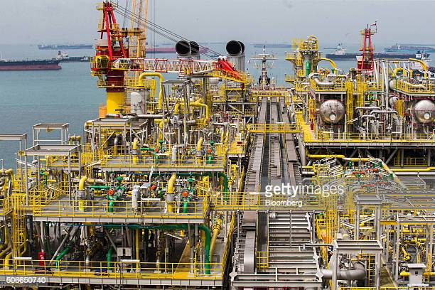 A worker walks along an elevated walkway on the Tullow Oil Plc Prof John Evans Atta Mills Floating Production Storage and Offloading vessel docked at...
