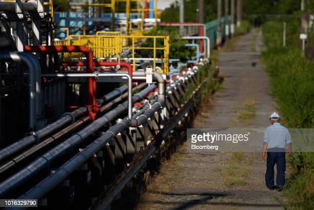 A worker walks along pipelines in Nagoya Japan on Tuesday July 31 2018 Japan is scheduled to release trade balance figures for July on Aug 16...