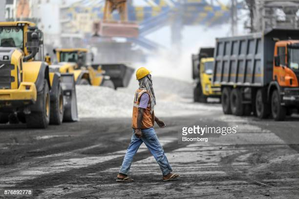 A worker walks along the dock as materials are unloaded from a ship not pictured at Krishnapatnam Port in Krishnapatnam Andhra Pradesh India on...