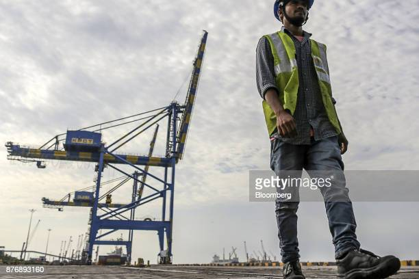 A worker walks along the dockside as gantry cranes stand in the background at Krishnapatnam Port in Krishnapatnam Andhra Pradesh India on Saturday...