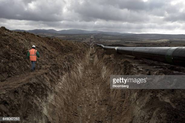 A worker walks along the edge of a pipe trench at the 6825km point during the construction of the Trans Adriatic gas pipeline in Chamilo Greece on...