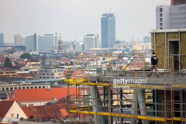Worker walks along the top of the main structure of the 50Hertz Transmission GmbH headquarter, as it is built on the construction site of Europacity,...