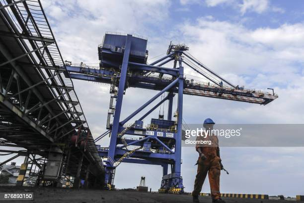A worker walks alongside a conveyor running past a gantry crane at Krishnapatnam Port in Krishnapatnam Andhra Pradesh India on Friday Aug 11 2017...