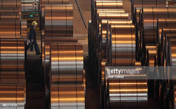 A worker walks among coils of galvanized steel at the ArcelorMittal Eko Stahl steelworks on January 26 2010 in Eisenhuttenstadt Germany ArcelorMittal...