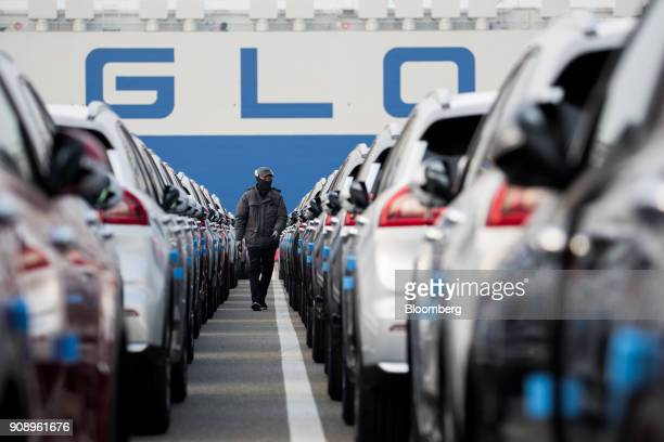 A worker walks among Kia Motors Corp vehicles bound for export at the port of Pyeongtaek in Pyeongtaek South Korea on Monday Jan 22 2018 Kia Motors...