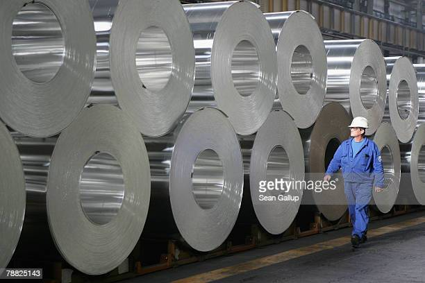 A worker walks among rolls of semifinished aluminum at the Alcoa aluminum factory October 24 2006 in Szekesefehervar Hungary Alcoa bought the factory...