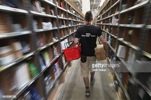A worker walks among shelves lined with goods at an Amazon warehouse on September 4 2014 in Brieselang Germany Germany is online retailer Amazon's...