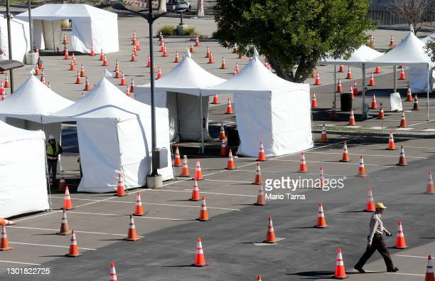 Worker walks at a large scale COVID-19 vaccination site under construction at Cal State Los Angeles on February 12, 2021 in Los Angeles, California....