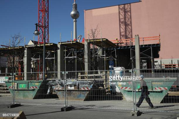 A worker walks at the construction site of the Grandaire apartments complex as the broadcast tower at Alexanderplatz stands behind on March 19 2018...
