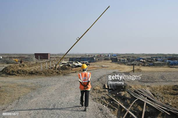A worker walks at the project site for a 920squarekilometer industrial area located on the DelhiMumbai Industrial Corridor near the village of...