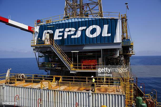 A worker walks beneath a giant Repsol logo on the Casablanca oil platform operated by Repsol SA in the Mediterranean Sea off the coast of Tarragona...