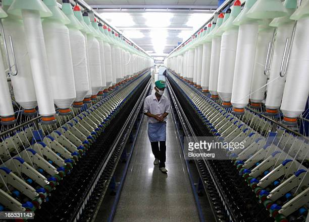 A worker walks between rows of spinning machines in the spinning area at a PT Sri Rejeki Isman factory in Sukoharjo Java Indonesia on Wednesday March...