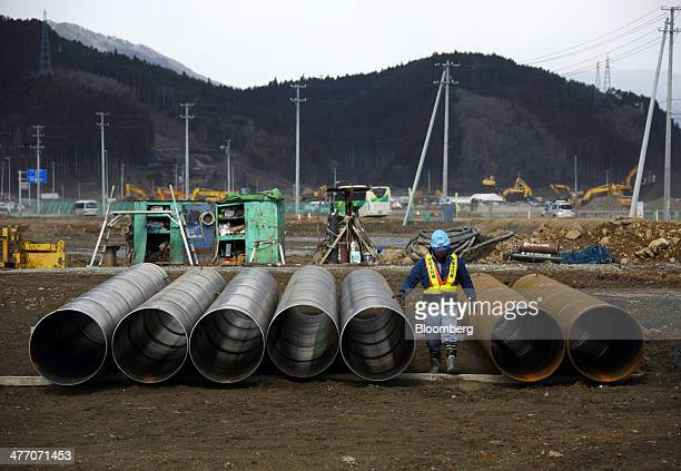 A worker walks between steel pipes at a construction site in Rikuzentakata Iwate Prefecture Japan on Thursday March 6 2014 Reconstruction of Tohoku...