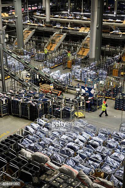 A worker walks between the conveyor belts and systems that handle the hundreds of thousands of items of mail that pass through the Royal Mail's...