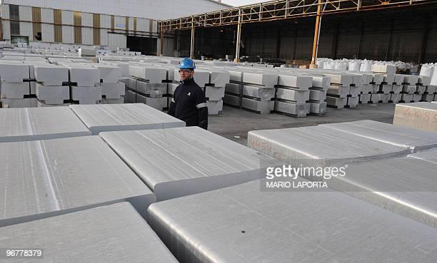 A worker walks by aluminium bars on February 15 2010 at the US aluminium company Alcoa's plant in Portovesme some 70 kilometers from Cagliari on the...
