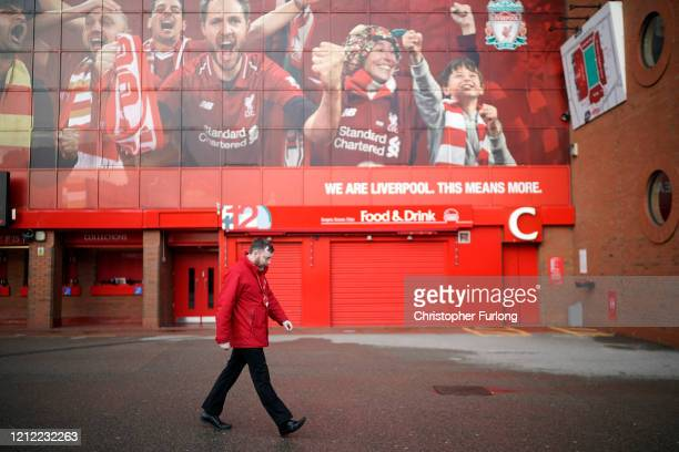 Worker walks by Anfield Stadium, the home Liverpool Football Club on March 13, 2020 in Liverpool, United Kingdom. It has been announced that all...