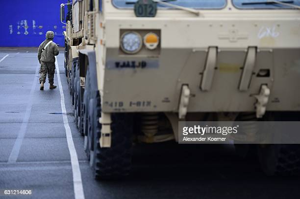 A worker walks by military vehicles while standing in line prior being loaded onto trains after being unloaded from ships two days before on January...