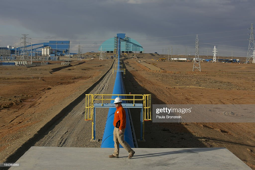 A worker walks by the blue conveyor belt that moves rock from the