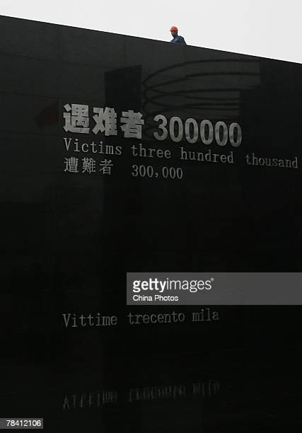 A worker walks by the monument commemorating victims who died in the Nanjing Massacre of 1937 during rehearsals for a ceremony to mark the 70th...