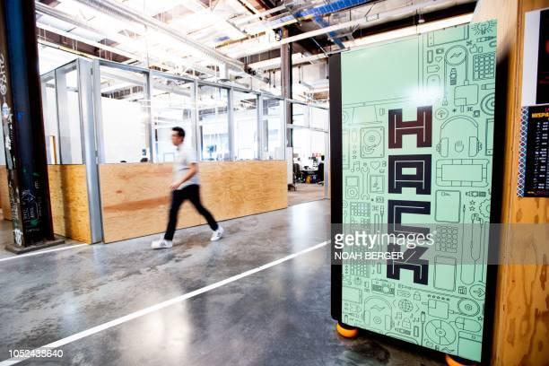 Worker walks down a hallway at Facebook headquarters on October 17 in Menlo Park, California. - The freshly launched unit at Facebook's Menlo Park...