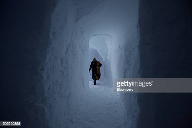 A worker walks down a passage to set up a bedroom inside the igloo hotel operated by IgluDorf GmbH on the Parsenn mountain in this arranged...