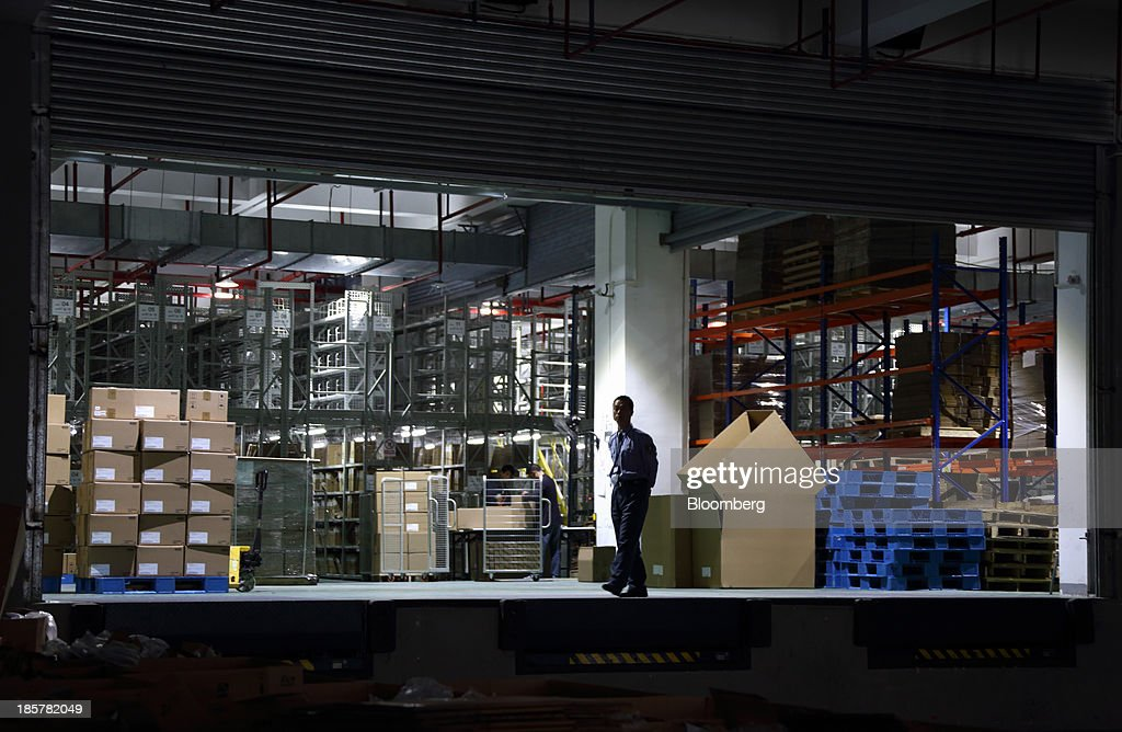 A worker walks in front of a storage area in a logistics center at China (Shanghai) Pilot Free Trade Zone's Pudong free trade zone in Shanghai, China, on Thursday, Oct. 24, 2013. The area is a testing ground for free-market policies that Premier Li Keqiang has signaled he may later implement more broadly in the world's second-largest economy. Photographer: Tomohiro Ohsumi/Bloomberg via Getty Images