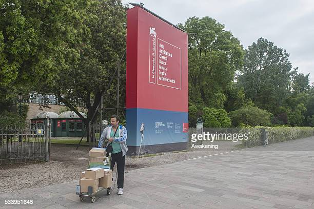 A worker walks in front of a street sign of the 15th Architecture Venice Biennale near the Giardini area on May 24 2016 in Venice Italy The 56th...