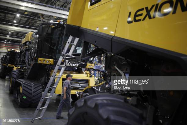 A worker walks in front of combine harvesters on the assembly line at the CLAAS of America Inc production facility in Omaha Nebraska US on Wednesday...