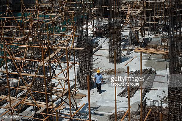 A worker walks inside a construction site in Beijing on July 13 2016 China's growth slipped to a new sevenyear low of 66 percent in the second...