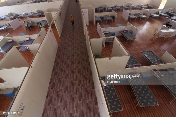 Worker walks inside a makeshift isolation center with 1008 beds for semi-critical COVID-19 patients in Mumbai, India on May 21, 2020. India continues...