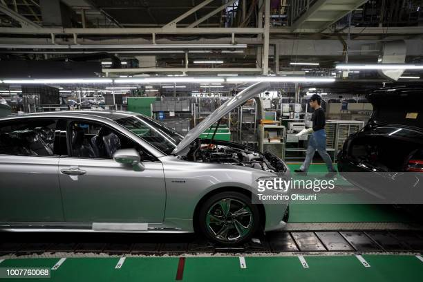 Worker walks near a Toyota Motor Corp Crown vehicle manufactured on the production line of the company's Motomachi factory on July 30, 2018 in...