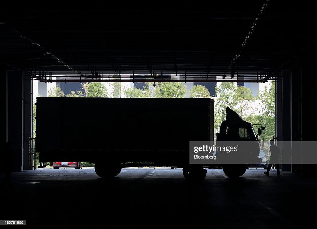 A worker walks near a truck carrying a shipping container in a logistics center at China (Shanghai) Pilot Free Trade Zone's Pudong free trade zone in Shanghai, China, on Thursday, Oct. 24, 2013. The area is a testing ground for free-market policies that Premier Li Keqiang has signaled he may later implement more broadly in the world's second-largest economy. Photographer: Tomohiro Ohsumi/Bloomberg via Getty Images