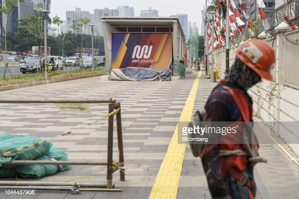 A worker walks near an entrance to an under construction Jakarta Mass Rapid Transit station in the Senayan area of Jakarta Indonesia on Thursday Sept...