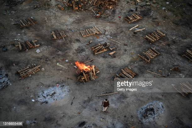 Worker walks near pyres for cremating the bodies of victims who died after contracting Covid-19 on the banks of the Ganges river May 06, 2021 in...
