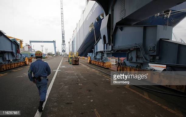 A worker walks near the Nippon Yusen KK's car transporter ship Auriga Leader at Mitsubishi Heavy Industries Ltd's Honmoku plant in Yokohama city...