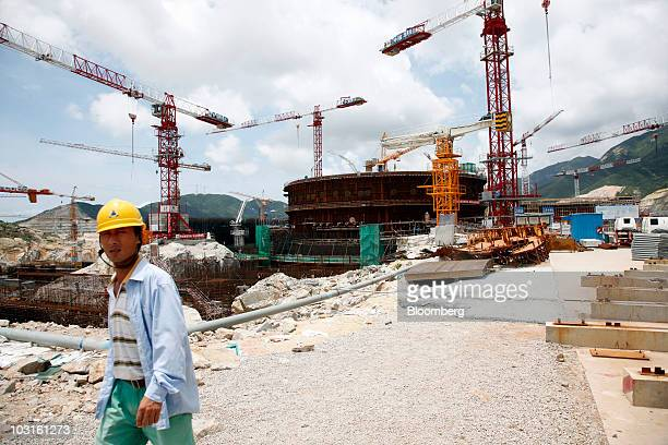 Worker walks near the Taishan 1 Areva SA EPR reactor at the China Guangdong Nuclear Power Group Co. Atomic plant in Taishan, Guangdong Province,...