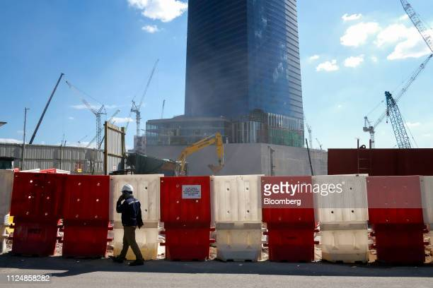 A worker walks near the under construction Exchange 106 building on the site of the Exchange TRX precinct in Kuala Lumpur Malaysia on Tuesday Feb 12...