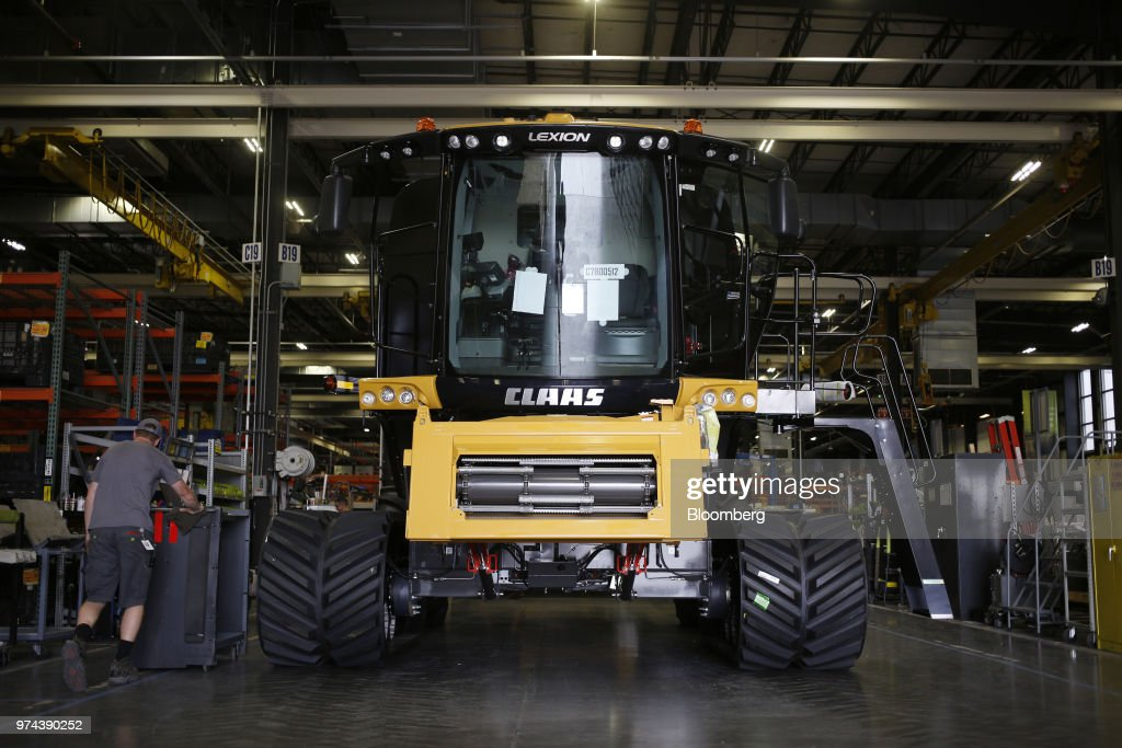 A worker walks next to a combine harvester on the assembly line at the CLAAS of America Inc. production facility in Omaha, Nebraska, U.S., on Wednesday, June 6, 2018. The Federal Reserve is scheduled to release industrial production figures on June 15. Photographer: Luke Sharrett/Bloomberg via Getty Images