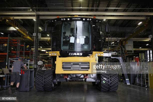 A worker walks next to a combine harvester on the assembly line at the CLAAS of America Inc production facility in Omaha Nebraska US on Wednesday...