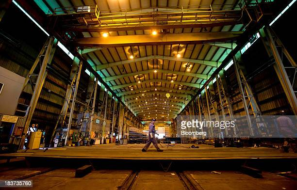 A worker walks on a portion of a barge under construction at the Seaspan Vancouver Shipyard in North Vancouver British Columbia Canada on Wednesday...
