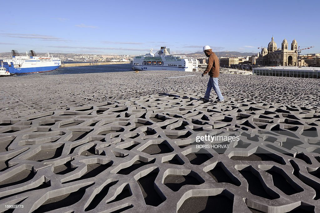 A worker walks on the roof of the Museum of Civilizations from Europe and the Mediterranean (MuCEM), designed by Italian architect Rudy Ricciotti, on January 11, 2013 in Marseille. Long plagued by a reputation for gang crime and lawlessness, France's port city of Marseille is hoping its year as the 2013 European Capital of Culture will finally give its image a makeover. The gritty Mediterranean city will kick off the festivities on January 12, 2013 with a downtown parade, fireworks and the opening of a slew of exhibitions. At background, ferries and Sainte-Marie Majeure cathedral also known as 'La Major'.