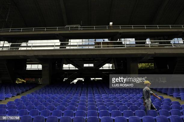 A worker walks on the stands the 'Pascual Guerrero' stadium in Cali department of Valle del Cauca Colombia on April 21 during the visit of the FIFA...