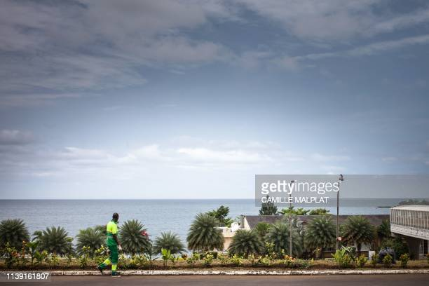 A worker walks on the street with a seaview in Sipopo nearly 16km from Malabo in Equatorial Guinea on April 20 2019 In Sipopo a seaside resort built...