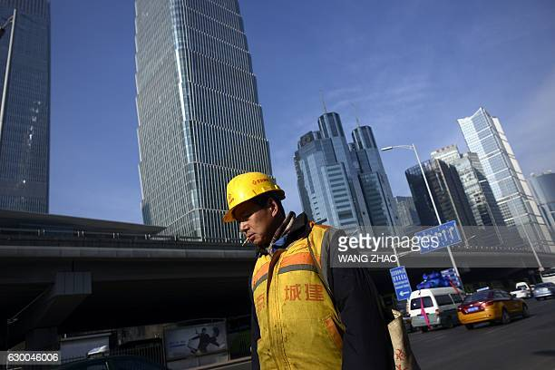 A worker walks outside a construction site in Beijing on December 16 2016 China's industrial output and retail sales growth both accelerated in...