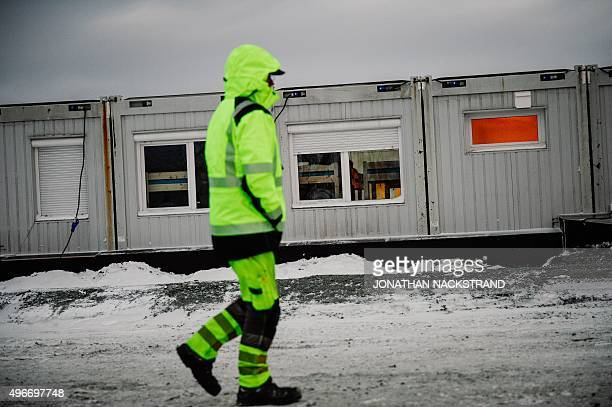 A worker walks outside the sleeping facilities at the arrival centre for refugees near the town on Kirkenes in northern Norway close to the border...